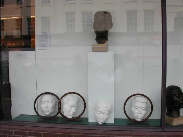 Left section of window in gallery showing sculptures by Laury Dizengremel